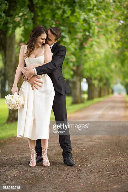 Bride and groom embracing in park
