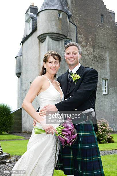 Bride and groom embracing outdoors, castle in background, portrait