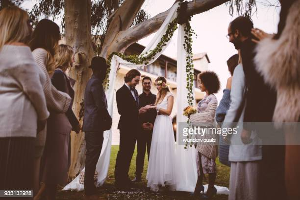 bride and groom exchanging wedding rings at ceremony with guests - wedding ceremony stock photos and pictures