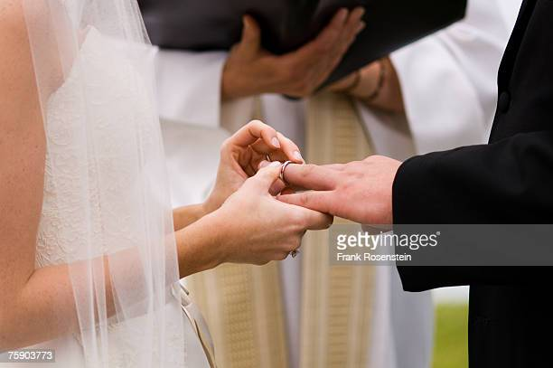 Bride and groom exchanging wedding rings, mid section