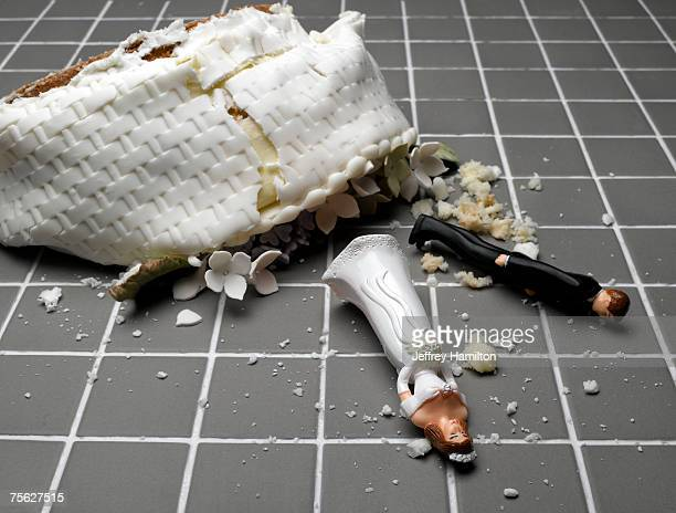 bride and groom figurines lying at destroyed wedding cake on tiled floor - wedding cake foto e immagini stock