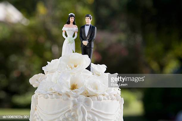 Bride and groom figurines on top of wedding cake, close-up