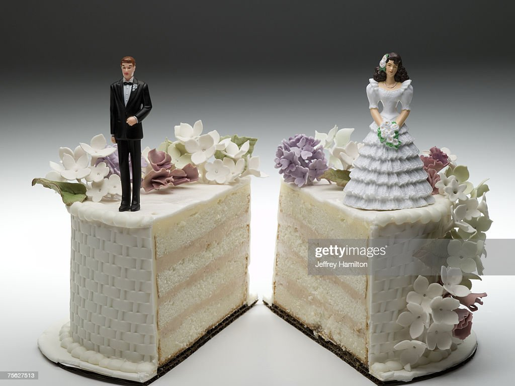 Bride and groom figurines standing on two separated slices of wedding cake : ストックフォト