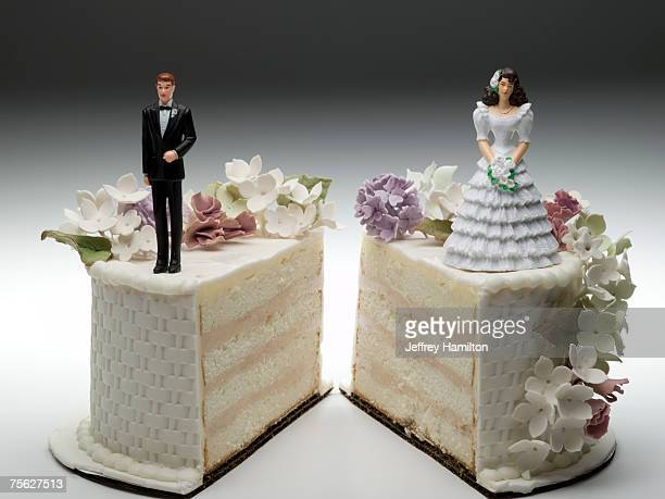 bride and groom figurines standing on two separated slices of wedding cake - wedding cake foto e immagini stock