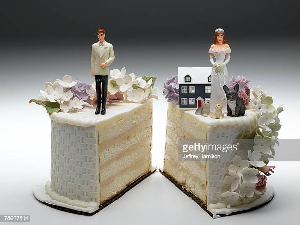 bride and groom figurines standing on two separated slices of wedding cake - lösung stock-fotos und bilder