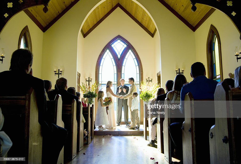 Bride and groom getting married during wedding ceremony in chapel : Stock Photo