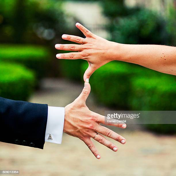 Bride and groom hands with their thumbs joined