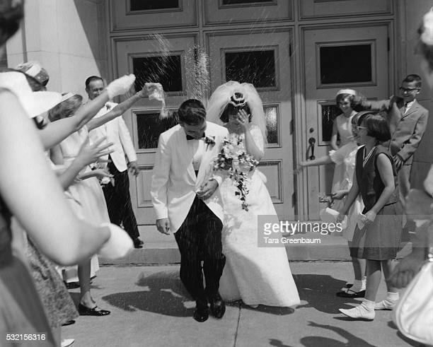 Bride and groom have rice thrown over them after wedding