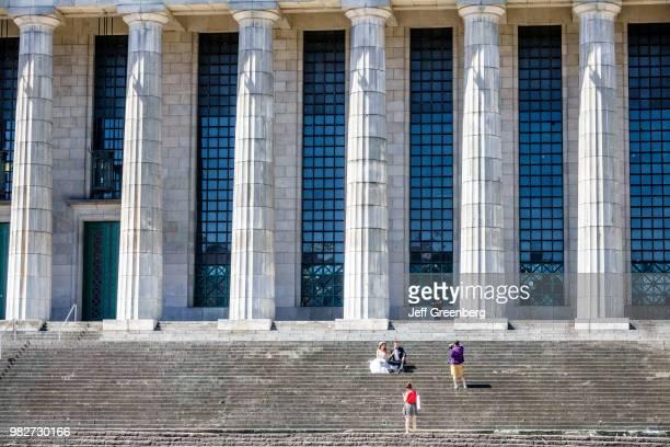 Bride and groom having photographs on the stairs outside the Facultad de Derecho de la Universidad de Buenos Aires Law School.