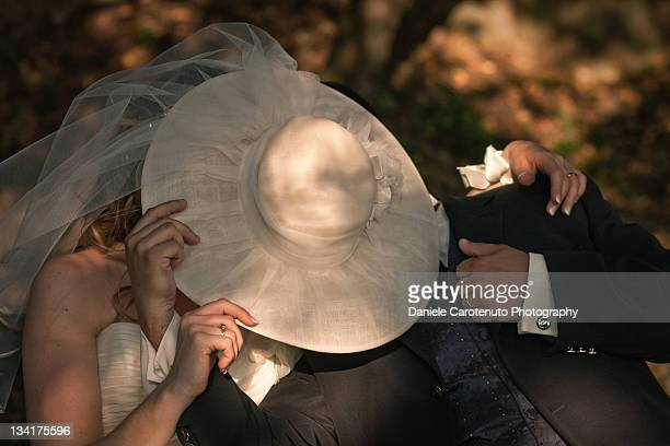 Bride and groom hiding behind hat