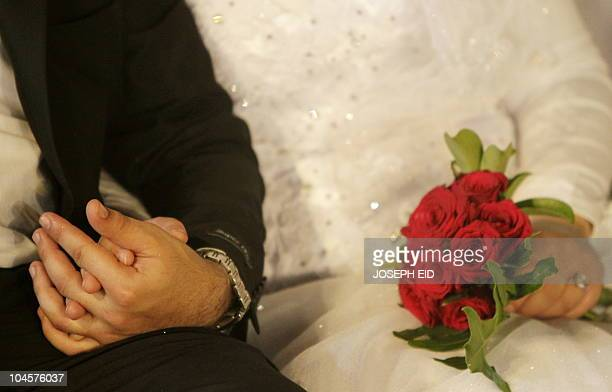 A bride and groom hold hands during a group wedding organised by the LebanesePalestinian Committee in the southern Lebanese port city of Sidon on...
