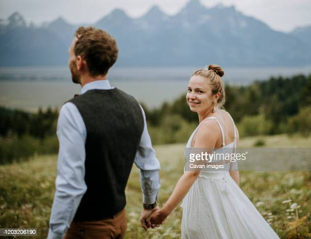 bride and groom hold hands while walking through field of flowers - beautiful wife pics stock pictures, royalty-free photos & images