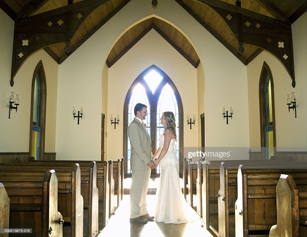 Bride and groom holding hands in chapel, side view : Stock Photo