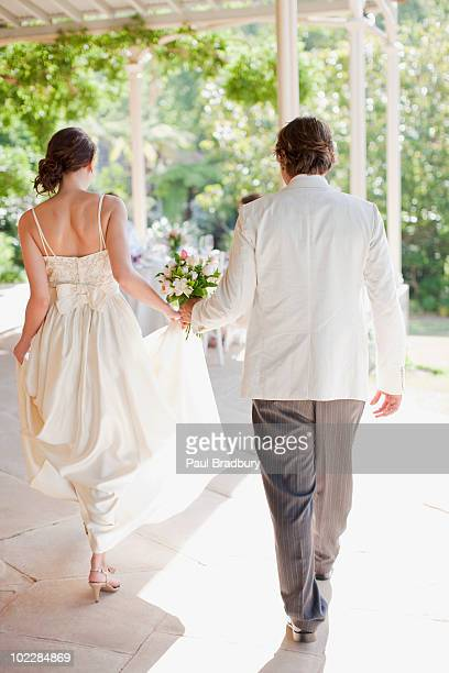 bride and groom holding hands - white tuxedo stock pictures, royalty-free photos & images