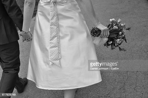 bride and groom holding hands while walking on street - coppia eterosessuale foto e immagini stock