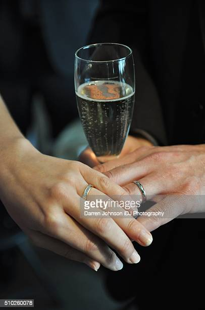 Bride and groom holding hands with new rings with glass of champagne