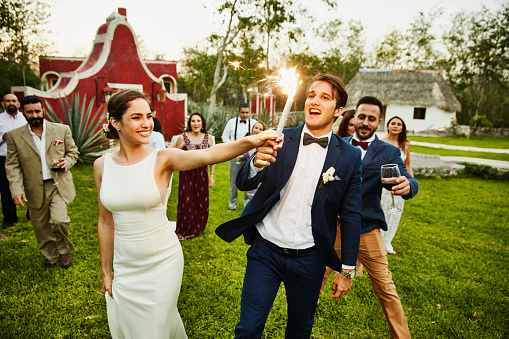 Bride and groom holding sparkler while celebrating during outdoor wedding reception with friends - gettyimageskorea