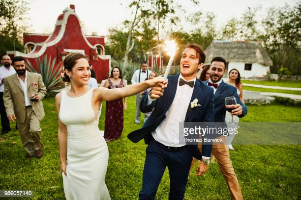 bride and groom holding sparkler while celebrating during outdoor wedding reception with friends - wedding stock pictures, royalty-free photos & images