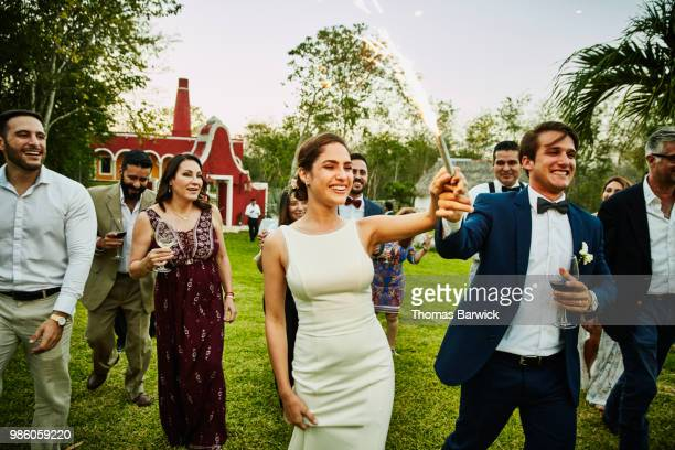 Bride and groom holding sparkler while celebrating during outdoor wedding reception