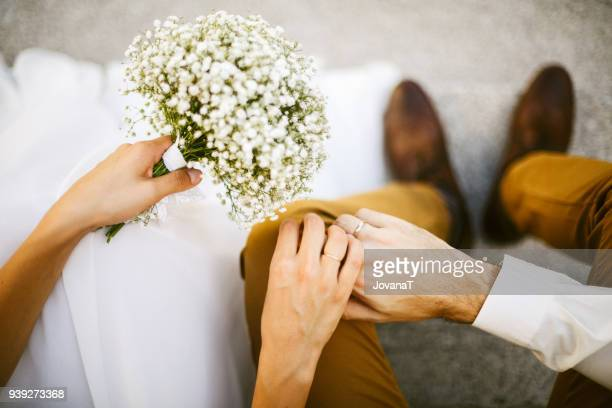 bride and groom holding their hands together - trouwen stockfoto's en -beelden