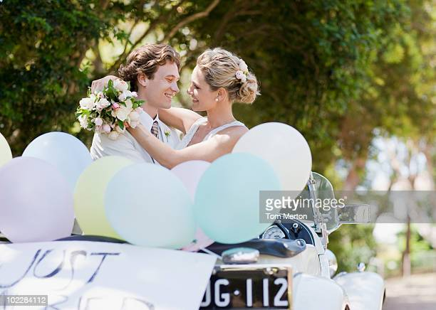 Bride and groom hugging in convertible
