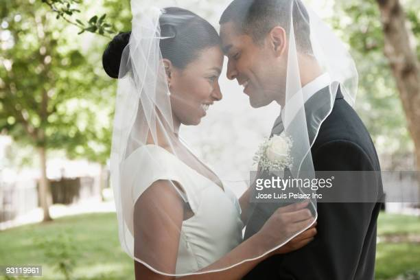 bride and groom hugging under veil - matrimonio foto e immagini stock