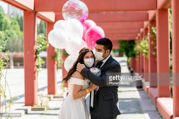 bride and groom in a face protection mask - wedding stock pictures, royalty-free photos & images