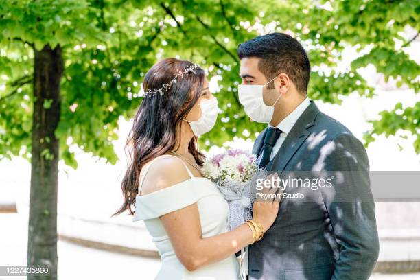 bride and groom in a face protection mask - matrimonio foto e immagini stock