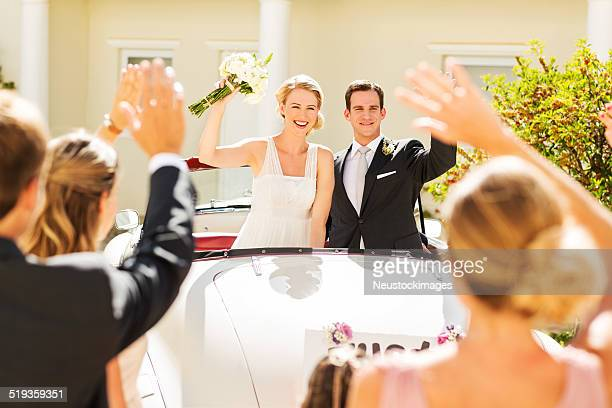 Bride And Groom In Car Waving At Wedding Guests