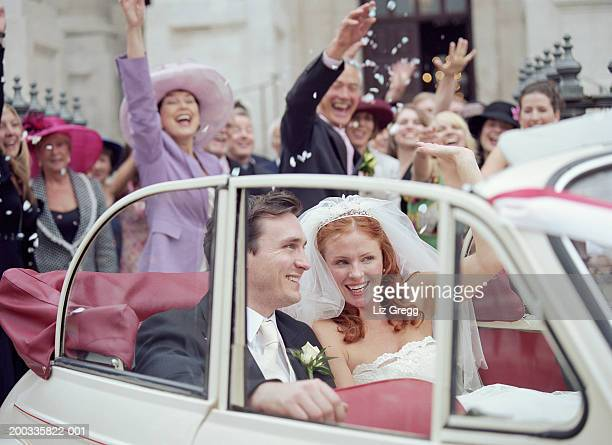 bride and groom in convertible car, wedding party waving in background - church wedding decorations stock pictures, royalty-free photos & images