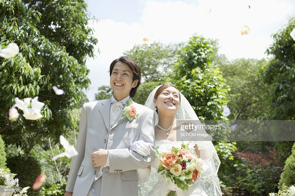 Bride And Groom In Flower Shower Smiling Walking Arm In Arm Stock