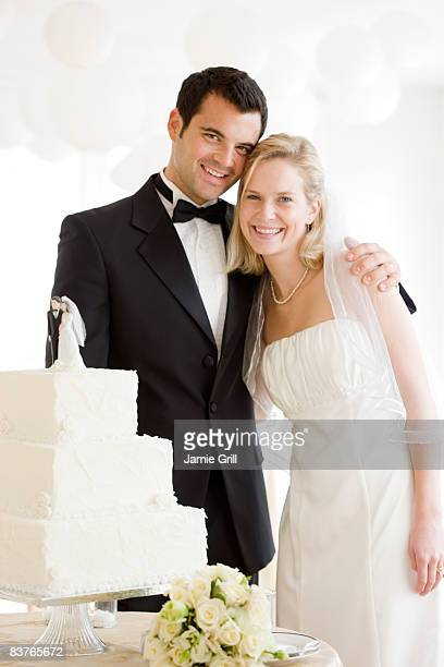 Bride and Groom in front of their wedding cake