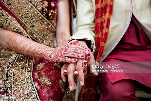 Bride and groom in traditional Indian wedding clothing with henna tattoos