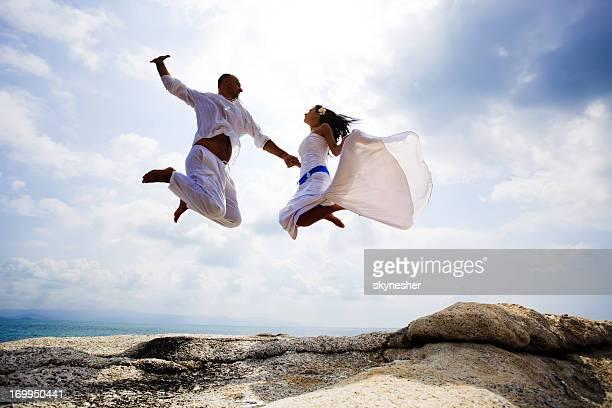 Sposa e lo sposo saltare contro il cielo.