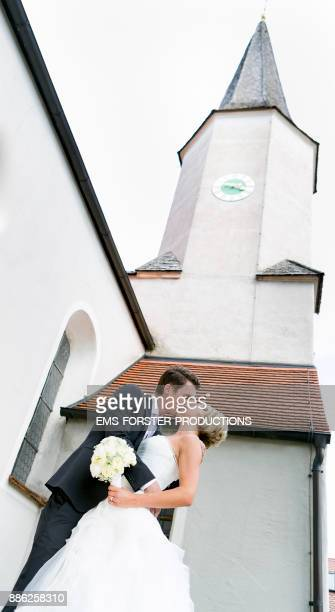 bride and groom kissing after the wedding ceremony outside in fron of the church