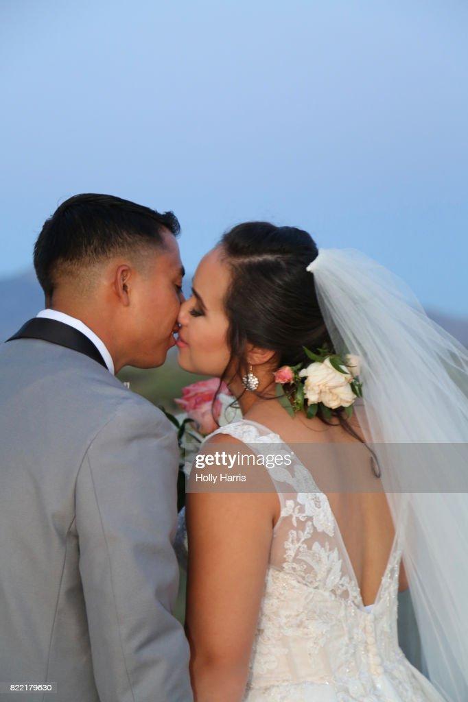 Bride and groom kissing at desert wedding at dusk : Stock Photo