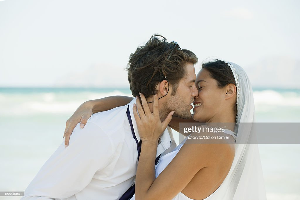 Bride and groom kissing at the beach : Stock Photo