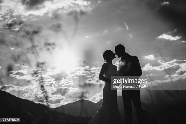 bride and groom kissing by mountains against dramatic sky - marriage stock pictures, royalty-free photos & images