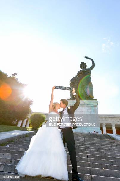 bride and groom kissing in fron of the Bavaria statue in Munich after wedding ceremony and holding a registration plate up in the air with 'just married' letters on it