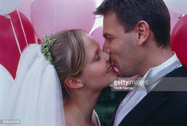 bride and groom kissing in front of balloons - tail coat stock pictures, royalty-free photos & images