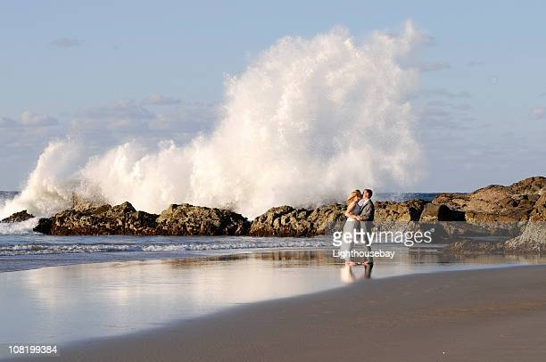 Bride and groom kissing in front of huge crashing wave