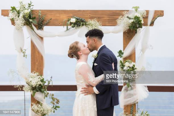 bride and groom kissing in front of wedding altar - altar stock pictures, royalty-free photos & images