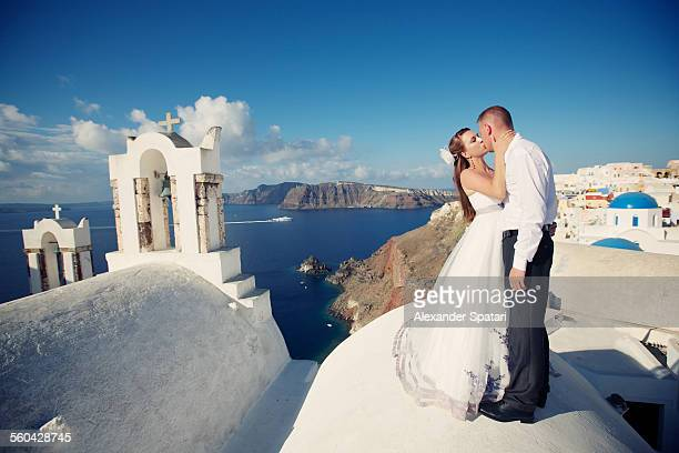 Bride and groom kissing in Santroini, Greece