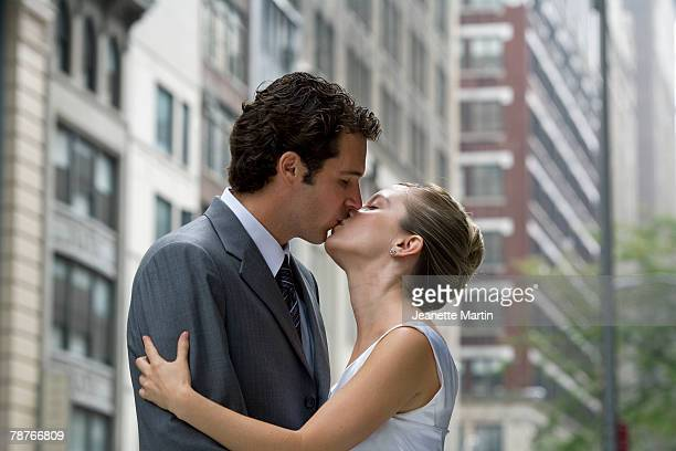 a bride and groom kissing in the street - bacio sulla bocca foto e immagini stock