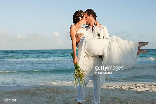Mariée et le marié embrassant sur la plage