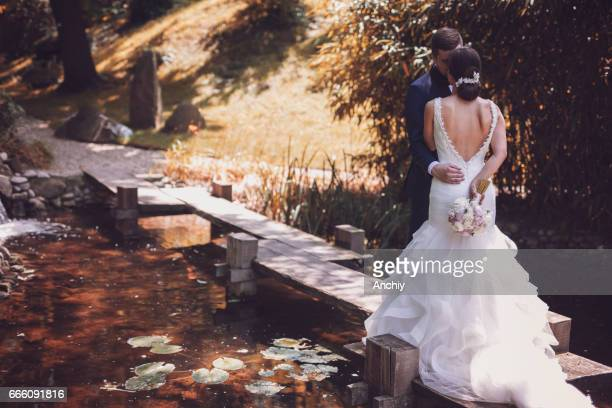 Bride and groom kissing on dock in the pond, engagement photo shoot