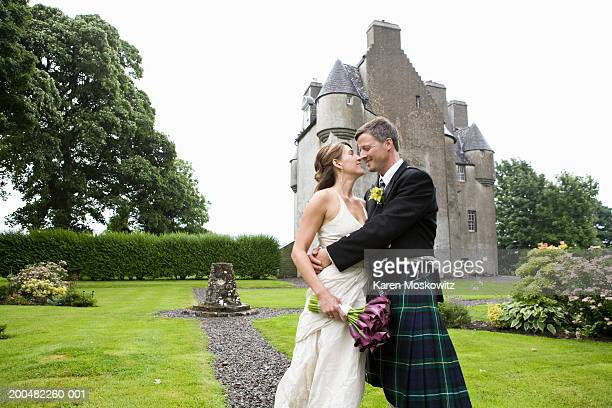 Bride and groom kissing on footpath in garden, castle in background