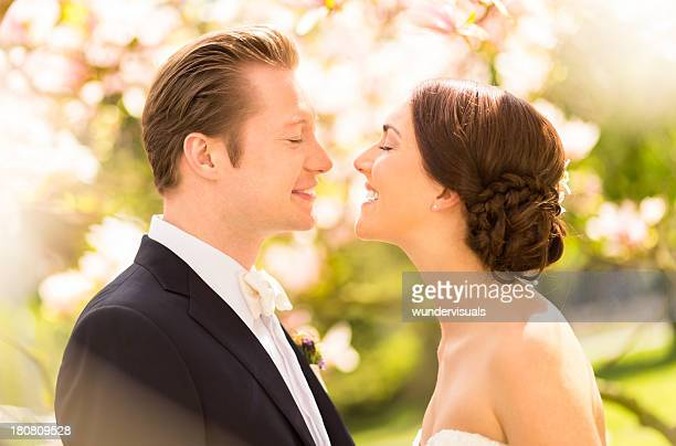 Braut und Bräutigam Küssen unter Magnolien-Blüten