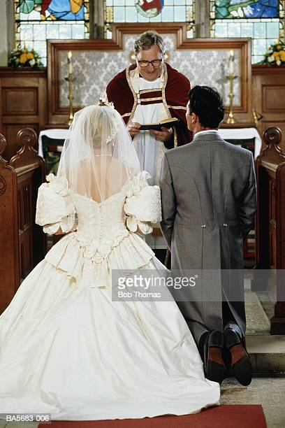 Bride and groom kneeling at altar with vicar, rear view