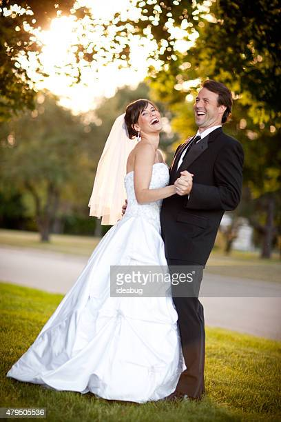 Bride and Groom Laughing and Dancing Together Outside